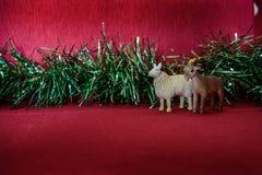 Simbolo delle pecore della sfuocatura del lamé della ghirlanda di anno su un fondo rosso Immagini Stock