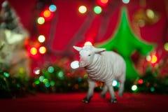 Simbolo delle pecore della sfuocatura del lamé della ghirlanda di anno su un fondo rosso Fotografie Stock Libere da Diritti