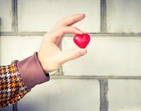 Simbolo di amore di forma del cuore nel giorno di biglietti di S. Valentino della mano dell'uomo Fotografia Stock
