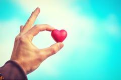 Simbolo di amore di forma del cuore nella festa di giorno di biglietti di S. Valentino della mano dell'uomo Immagine Stock Libera da Diritti