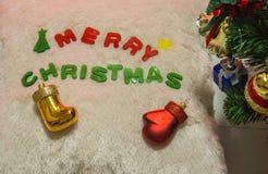 Simbolo di Buon Natale - calzino e guanto con il fondo dell'albero di Natale Immagine Stock