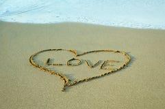 Simbolo di disegno del cuore sui precedenti della sabbia alla spiaggia fotografia stock