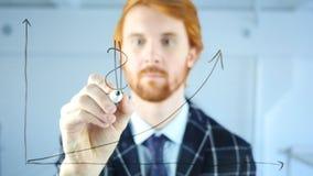 Simbolo di dollaro del disegno dell'uomo sul grafico di crescita su vetro trasparente, capelli rossi Fotografia Stock Libera da Diritti