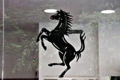 Simbolo di Ferrari e della vetrina di un deposito di Ferrari fotografie stock libere da diritti
