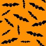 Simbolo di Halloween Modello senza cuciture dei pipistrelli di volo Pipistrelli neri su fondo arancio Siluetta fumetto Illustrazi royalty illustrazione gratis