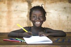 Simbolo di istruzione: Grande sorriso a trentadue denti sulla ragazza africana della scuola gorge Fotografia Stock