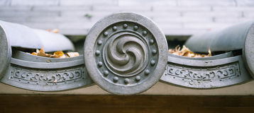 Simbolo di Mitsudomoe sulle mattonelle di tetto buddisti shintoiste del santuario, Giappone Immagini Stock