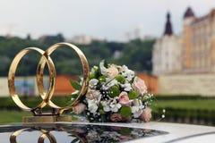 Simbolo di nozze - due hanno attraversato gli anelli sul tetto dell'automobile e del Th Fotografia Stock Libera da Diritti