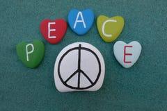 Simbolo di pace su una pietra con il testo di pace sulle lettere colorate della pietra del cuore immagini stock libere da diritti