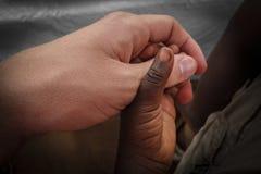 Simbolo di povertà - pace delle mani amiche dell'Africa Piccole sedere africane Immagini Stock