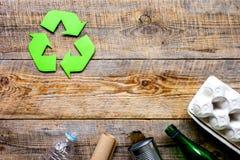 Simbolo di riciclaggio dei rifiuti con immondizia sul modello di legno di vista superiore del fondo Fotografia Stock