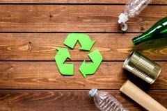 Simbolo di riciclaggio dei rifiuti con immondizia sul modello di legno di vista superiore del fondo Immagini Stock Libere da Diritti