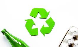 Simbolo di riciclaggio dei rifiuti con immondizia sulla vista superiore del fondo bianco Fotografie Stock