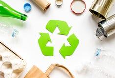Simbolo di riciclaggio dei rifiuti con immondizia sulla vista superiore del fondo bianco Immagine Stock