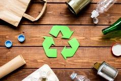 Simbolo di riciclaggio dei rifiuti con immondizia sulla vista superiore del fondo di legno Fotografia Stock