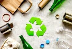 Simbolo di riciclaggio dei rifiuti con immondizia sulla vista superiore del fondo di pietra Fotografia Stock