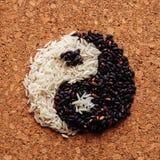 Simbolo di yin yang di riso in bianco e nero sulla superficie dei precedenti del sughero Immagini Stock