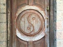Simbolo di yin yang scolpito sulla porta di legno immagini stock libere da diritti