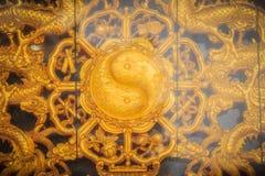 Simbolo dorato dell'yin yang sulla parete del tempio cinese in Tha Fotografia Stock