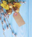 Simbolo dorato delle uova della quaglia, alstroemeria del salice su un'etichetta di legno blu del fondo Immagine Stock Libera da Diritti