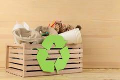 Simbolo e rifiuti di Eco nella scatola riciclaggio Riciclaggio dei rifiuti su fondo di legno naturale immagine stock