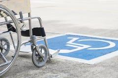 Simbolo e sedia a rotelle di handicap della pavimentazione fotografia stock libera da diritti