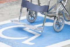 Simbolo e sedia a rotelle di handicap della pavimentazione Immagini Stock