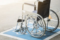 Simbolo e sedia a rotelle di handicap della pavimentazione nell'ospedale fotografia stock