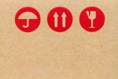 simbolo fragile rosso su cartone. Fotografie Stock