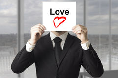 Simbolo nascondentesi del cuore di amore del fronte dell'uomo d'affari Fotografie Stock Libere da Diritti