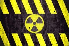 Simbolo radioattivo del pericolo di radiazione ionizzante con le bande gialle e nere dipinte su un muro di cemento massiccio Fotografie Stock Libere da Diritti