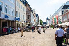 Simeonstrasse street and view of St Gangolf Church. TRIER, GERMANY - JUNE 28, 2010: people on Simeonstrasse street and view of St Gangolf Church in Trier city Royalty Free Stock Image