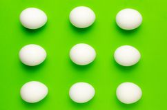Simetría de los huevos blancos en fondo verde claro brillante foto de archivo