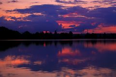 Simetría hermosa de la puesta del sol sobre el agua de un lago fotografía de archivo libre de regalías