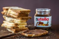 SIMFEROPOL, UCRÂNIA - 3 DE OUTUBRO DE 2018: Cortado do frasco de mármore da propagação do pão e da avelã de Nutella na tabela de  fotos de stock royalty free