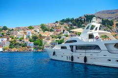 SIMI ISLAND, GREECE, JUNE 25, 2013: View on beautiful classic white yacht, Greek sea port, gingerbread houses on island hills, blu royalty free stock photography
