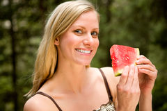 Similing Woman with Watermelon. A portrait of a blonde woman eating a watermelon stock photo