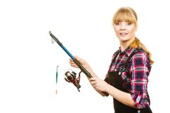 Similing woman wearing check shirt holding fishing rod. Fishing concept. Attractive woman in dungarees, pink check shirt holding rod.  background Royalty Free Stock Photo