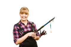 Similing woman wearing check shirt holding fishing rod Stock Photo