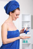 Similing woman wearing a towel using moisturiser stock photo