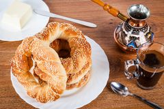 Simit And Coffee. Fresh Turkish simit and a cup of black coffee. Delicious Turkish bagels with sesame seeds Royalty Free Stock Photos
