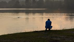 Simma den unga mannen och en skyttekamerakvinna på solnedgången lager videofilmer