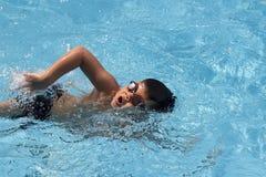 Simmar den främre krypandet för den asiatiska pojken i simbassäng Royaltyfri Bild