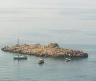 Simmare och nöjeyachter nära stenön i fjärden av Petrovac, Montenegro Royaltyfri Bild