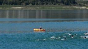 Simmare som simmar i en triathlon i en sjö om den soliga dagen lager videofilmer