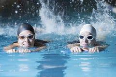 Simmare som simmar med ett badbräde Fotografering för Bildbyråer