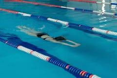 Simmaren hoppar från plattformen som hoppar en simbassäng Royaltyfri Foto