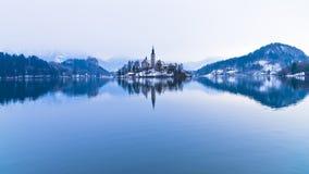 Simmetria perfetta di un lago e di una chiesa su una piccola isola, alpi sanguinate e slovene Fotografia Stock Libera da Diritti
