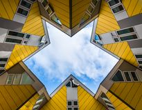 Simmetry Gleam between Yellow Cubic houses and apartments in Rotterdam. The Netherlands. Simmetry Gleam of cloudy sky between Yellow Cubic houses and apartments royalty free stock photos