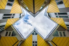 Simmetry Gleam between Yellow Cubic houses and apartments in Rotterdam. The Netherlands. Simmetry Gleam of cloudy sky between Yellow Cubic houses and apartments stock images